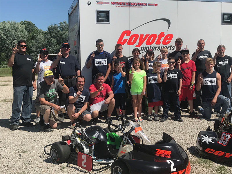 Racers gather for a group photo in front of the Coyote Motorsports hauler at Mid-State