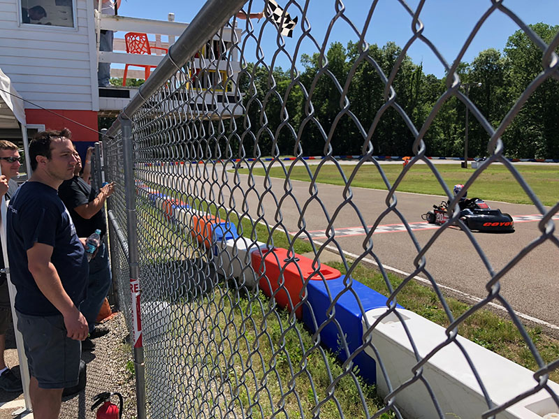 Coyote's Jim Lipari watches from the Mid-State fence as Justin Wishard (No. 20) races past